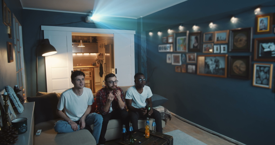 Excited young multiethnic students watch sports game on TV together at home using projector big screen slow motion. | Shutterstock HD Video #1037462138