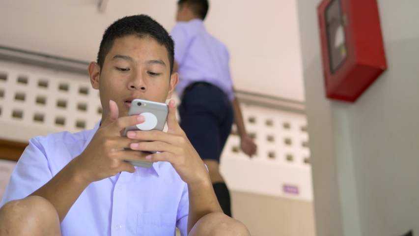 An Asian male high school student in a white uniform, who is a lot of addicted to games, is playing exciting games on his mobile phone and sitting on the school stairs. | Shutterstock HD Video #1037486498