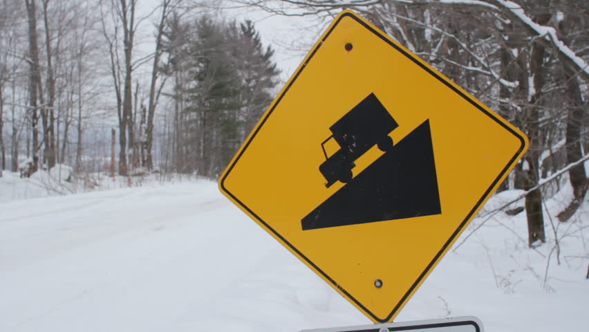 steep hill sign. winter. yellow, diamond shaped sign warns of