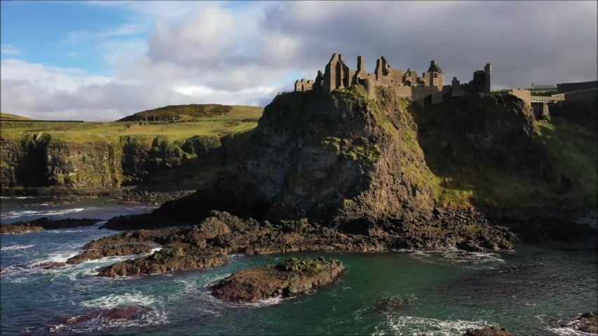 Infamous Dunluce Castle on the Co. Antrim coast of N. Ireland and surrounding coastline captured by drone.   Shutterstock HD Video #1037528948