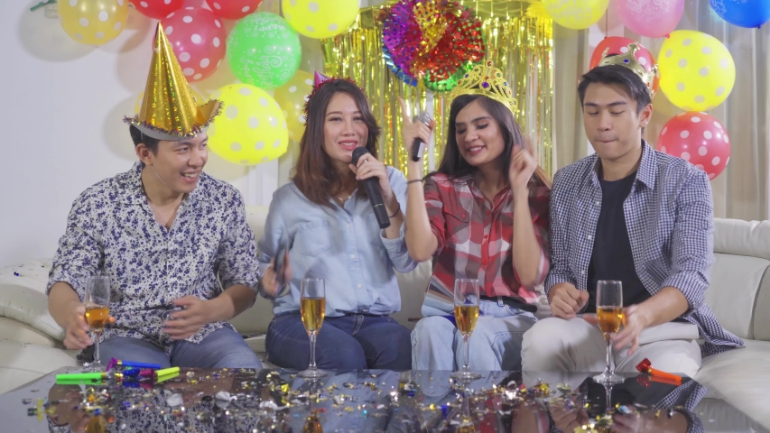 Group of cheerful people celebrating birthday party while singing and dancing together on sofa with festive decoration at home. Shot in 4k resolution