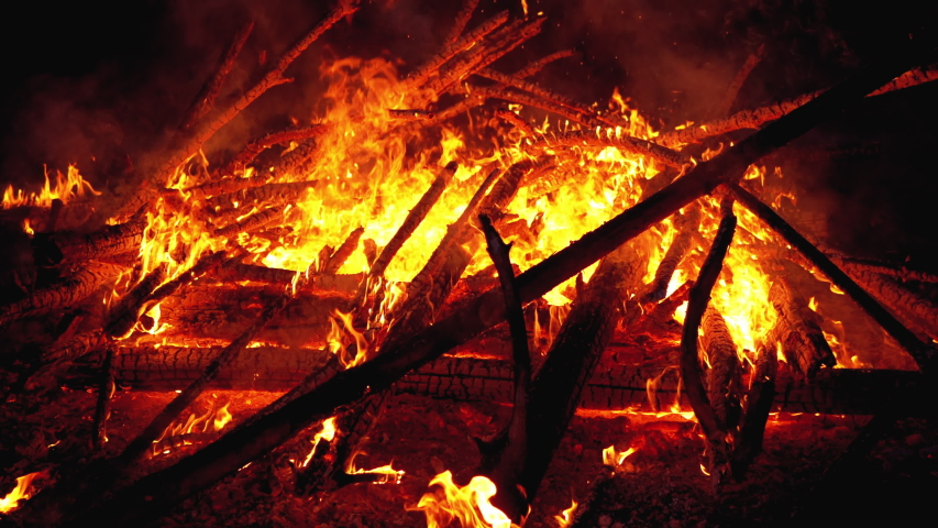 Big Bonfire of the Logs Burns at Night in the Forest. Large Fire Brightly Burning on Black Background. Close-up. Red Flames and Embers of fire climb up. Heated coal beautifully shimmering red glow. 4K | Shutterstock HD Video #1037568158
