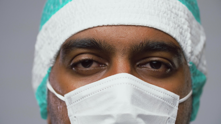 Medicine, science and surgery concept - close up of indian male doctor, surgeon or scientist in protective mask over grey background | Shutterstock HD Video #1037657558