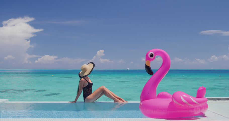 Travel Vacation Woman in bikini and inflatable pink flamingo float pool toy mattress in swimming pool. Girl sunbathing enjoying holidays at resort pool living luxury lifestyle. | Shutterstock HD Video #1037758688