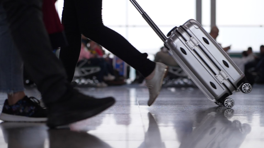 Passenger woman walk with silver case at airport, group of people come towards, low side shot, slow motion camera show legs of travellers going at terminal hall | Shutterstock HD Video #1037771708