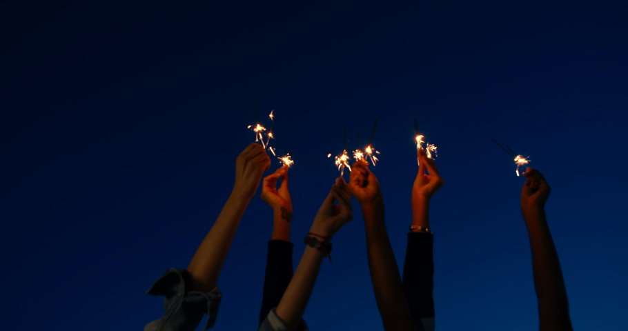Close up of hands of girls holding sparklers . Group of friends celebrating waving sparkler fireworks dancing enjoying party having fun holiday celebration at evening social gathering on rooftop 4k | Shutterstock HD Video #1037828738