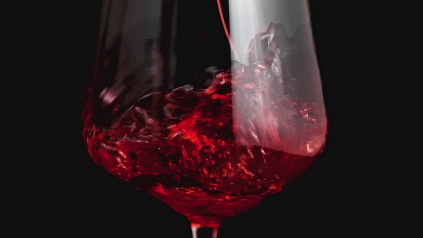 Red wine forms beautiful wave. Wine pouring in wine glass over black background. Close-up shot. Slow motion of pouring red wine from bottle into goblet. Low key | Shutterstock HD Video #1038128318