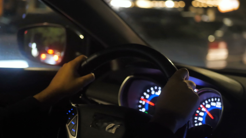 Close up view from back seat of male hands on steering wheel inside of automobile driving on city road. Driver   Shutterstock HD Video #1038243338