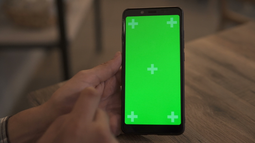 Close-up of a Man's Hand Holding Green Mock-up Screen Smartphone. Using app. Modern Mobile Phone. In the Background Cozy Living Room or Home Office. | Shutterstock HD Video #1038247088