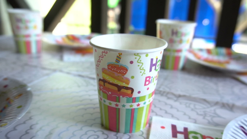 Cardboard disposable tableware. Side view .. Festive design. Plate, cup and napkin. Children's birthday. Preparation for the holiday. Table setting. Recycled material. Slow motion camera. | Shutterstock HD Video #1038248708