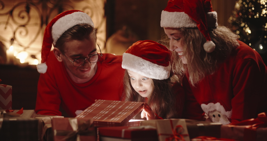 Caucasian family of three sitting in decorated room near christmas tree, little girl opening her christmas gift with something special - christmas spirit, togetherness concept 4k footage | Shutterstock HD Video #1038340508