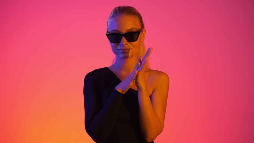 Attractive caucasian blonde young girl rubbing her palms within temptation looking to camera. Rubbing hands in vivid neon light with red and blue colors at gradient background | Shutterstock HD Video #1038437108