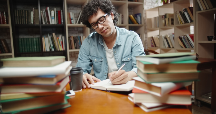 Asian student with curly hair is in library, sits at desk full of books. Guy wearing glasses preparing for exam and studying - education concept close up 4k   Shutterstock HD Video #1038540128