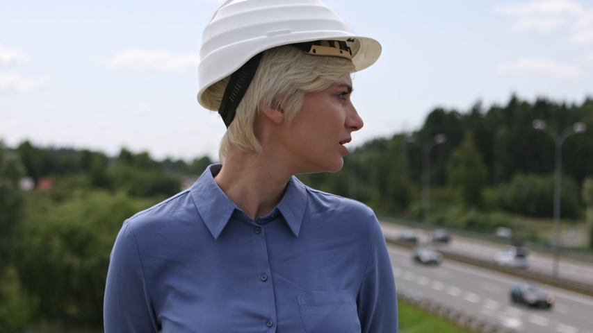 Static medium shot of a middle aged construction worker lady wearing a protective helmet with the highway blurred in the background | Shutterstock HD Video #1038563978