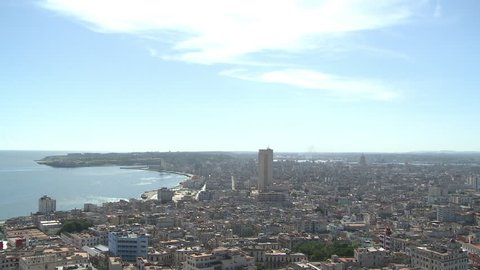 Aerial, panoramic shot of Havana Cuba. The camera pans from the sky to reveal the central city district of Havana and Caribbean Sea in the distance.