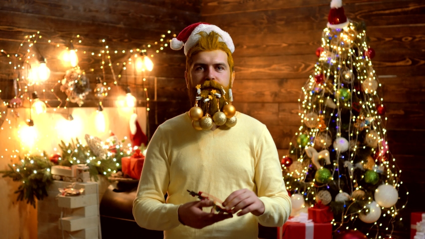 Hipster Santa Claus Christmas preparation. Attractive bearded hipster. Christmas Celebration. Christmas party. Christmas man in Santa hat. Portrait of surprised and funny man. Santa fun   Shutterstock HD Video #1038732488