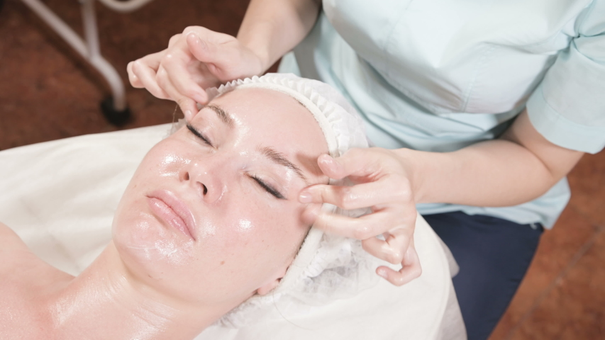 Girl beautician in a mask and gloves makes a salubrious facial massage to an attractive woman. New generation cosmetology massage | Shutterstock HD Video #1038750938
