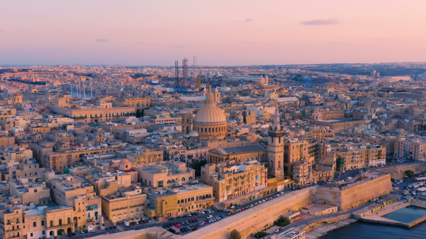 Aerial circling view of Valletta, Malta with Basilica of Our Lady of Mount Carmel at sunset | Shutterstock HD Video #1038761468