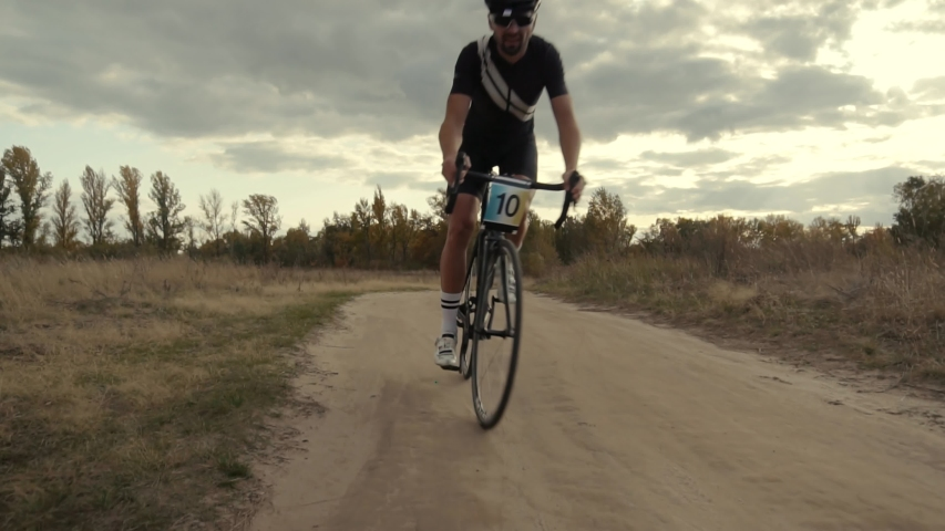 Cyclist Riding On Gravel Bike In Slow Motion.Cycling Race On Gravel Road.Bicycle Racing On Trail. Leader On  Race Hurries To Finish Line.Strong Professional Cyclist Athlete On Crosscoutry Competition