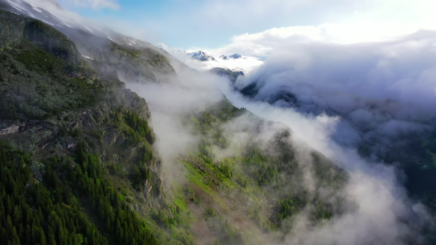Aerial: Picturesque Village in Cloudy Valley Under Sunlit Mountain - Mount Blanc, France #1038924548