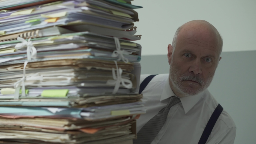 Stressed frustrated businessman sitting at office desk and peeking from behind a pile of paperwork, overwork and management concept