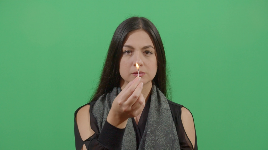Woman Lighting A Match And Showing It To The Viewer. Studio Isolated Shot Against Green Screen Background | Shutterstock HD Video #1039150868
