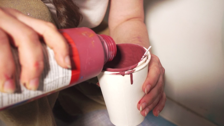 Person adds thick red paint to container for decorating | Shutterstock HD Video #1039179668