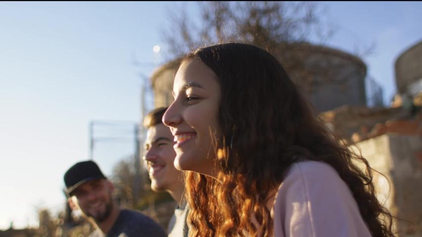 Three happy friends sitting outdoors | Shutterstock HD Video #1039235258