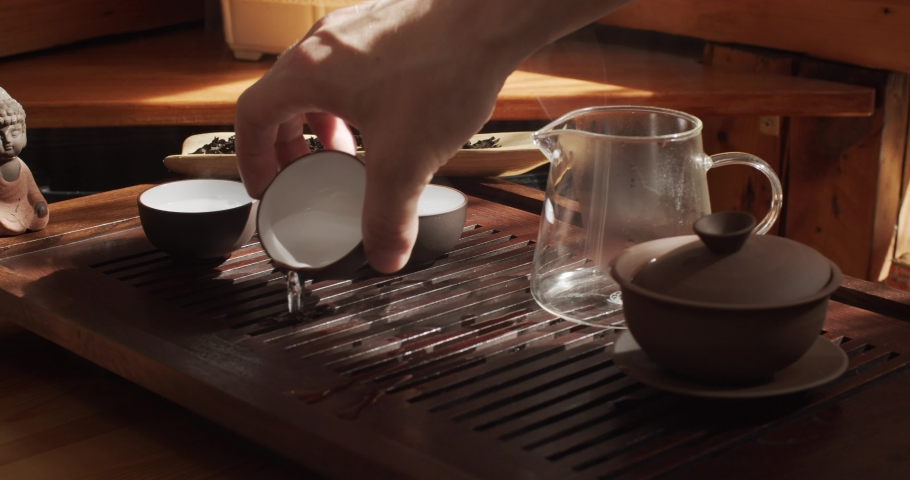 Process of tea ceremony indoors close up natural sunlight slow motion 4k. Male hands no face pouring off hot water into special tray preparing Chinese energetic drink. Eastern culture tools rules  | Shutterstock HD Video #1039265318