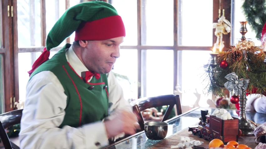 Hungry male elf eating dessert at Christmas. Elf in green costume drink tea with pastries sitting next to Santa indoors. | Shutterstock HD Video #1039326188