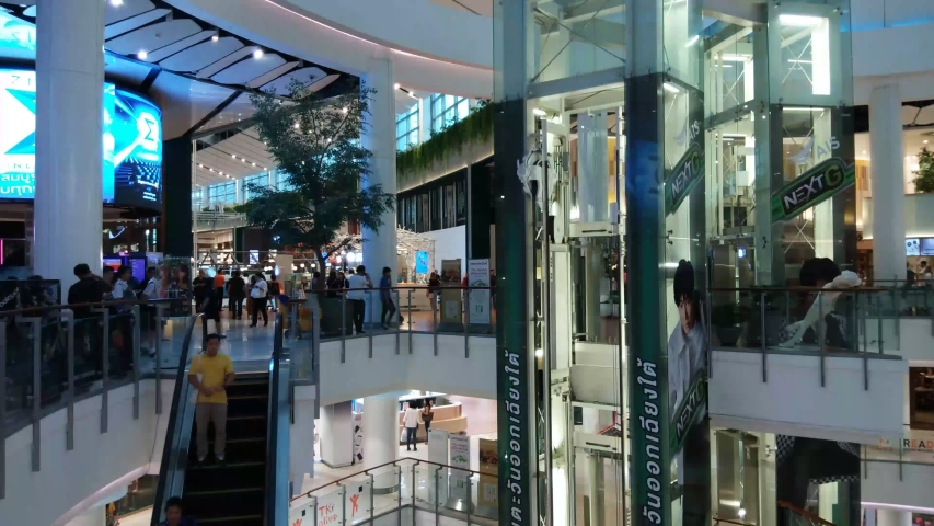 BANGKOK THAILAND - SEPTEMBER 6,2019 : time lapse of an escalator and people passing in a big round square at a mall. #1039370768