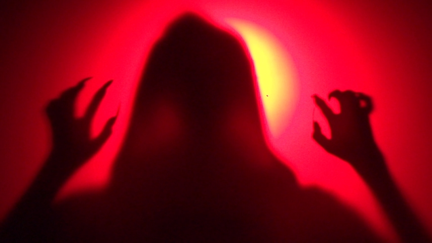 Mystical creepy creature with long nails. Halloween scene in red light. A silhouette of a ghost behind glass. Shot in defocus. | Shutterstock HD Video #1039557878