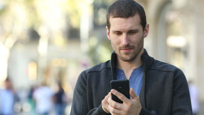 Front view of a serious adult man checking smart phone standing in the street | Shutterstock HD Video #1039589648