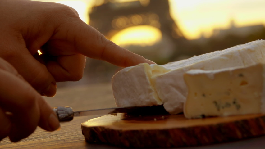 Hand takes a piece of brie cheese from a wooden board on the background of the Eiffel Tower, Paris, France | Shutterstock HD Video #1039589678