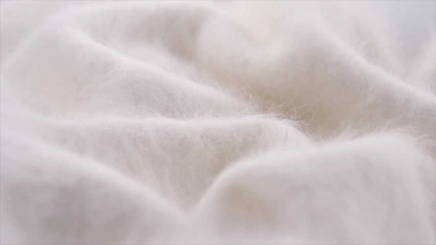 Soft Wool background. Alpaca wool mohair clothes texture closeup. Natural Cashmere Soft and fluffy merino wool macro shot. Woolen fabric rotation backdrop. Slow motion UHD 4K | Shutterstock HD Video #1039779158