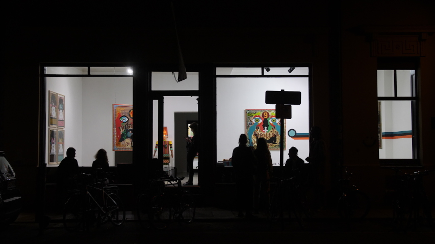 Berlin, Germany, September 2019. People hanging out in front of art gallery at night.
