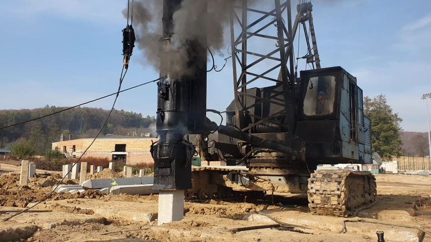 Machine drives into the ground piles construction. Construction of the Foundation of reinforced concrete structures. | Shutterstock HD Video #1040440688