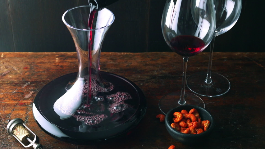 Red wine is decanted next to cashew nuts on rustic wooden table | Shutterstock HD Video #1040630738