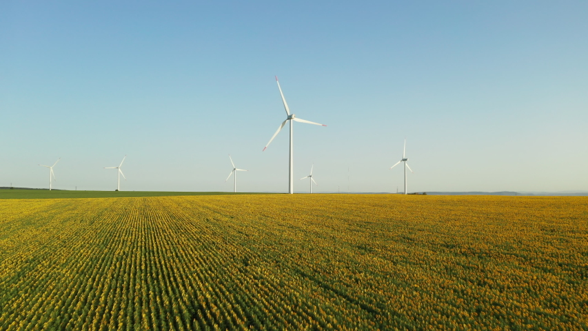 Aerial view drone flying forward large wind turbine with rotating blades against the background of sown green agricultural fields and windy park. Ecology. Alternative energy | Shutterstock HD Video #1040687228
