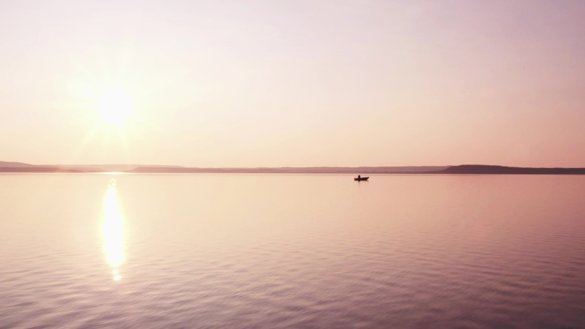 Silhouette of fishermen alone in a boat swimming on a big lake / sunset background - aerial drone view | Shutterstock HD Video #1040698478