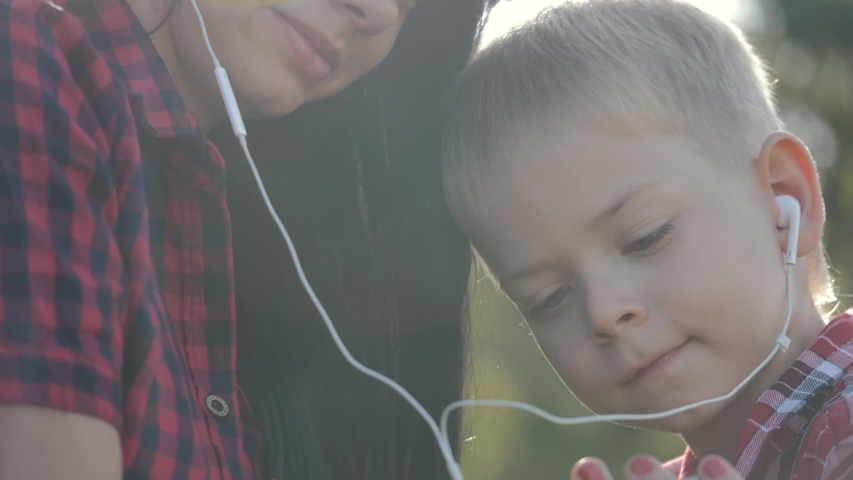 Happy family mom with her son listen to music on headphones on a smartphone. Family listens to music outdoors in a field in the sun. | Shutterstock HD Video #1040817008