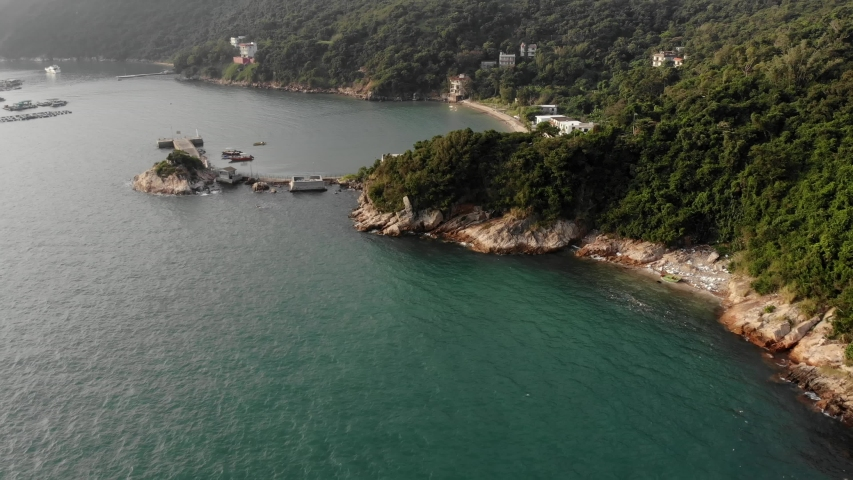 Aerial view the coast of the island of Lamma, in the frame of a villas on the seashore, pier. Waves breaking on a rocky shore. Hong Kong   Shutterstock HD Video #1040818928