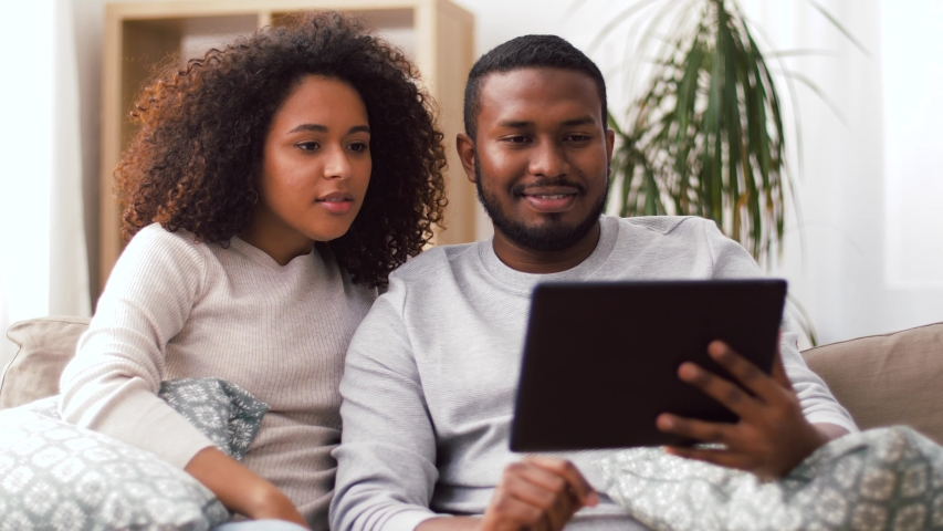 Technology, communication and people concept - smiling happy african american couple with tablet having video call at home. | Shutterstock HD Video #1040826458