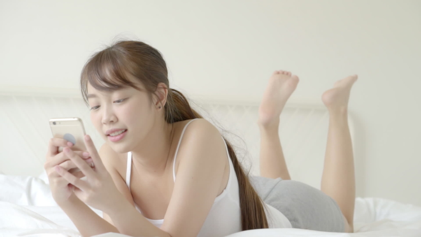 Beautiful portrait young asian woman smiling lying look smart mobile phone reading social network with enjoy on bed at bedroom, girl chat messaging to internet online, communication concept. | Shutterstock HD Video #1040839808