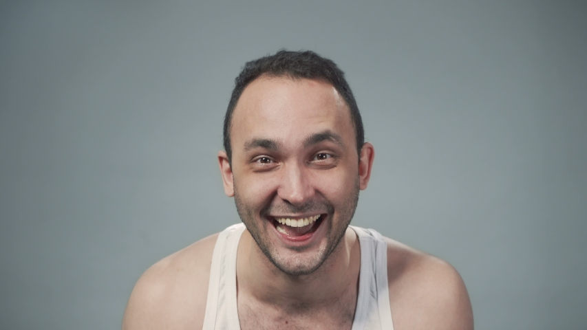 Video of laughing bristly man on gray background | Shutterstock HD Video #1040914118