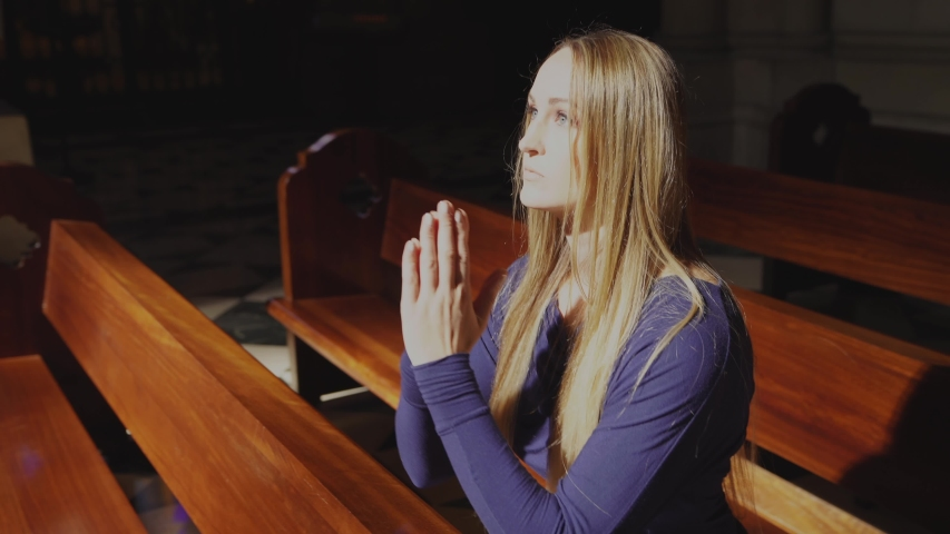 This video shows a young caucasian woman kneeling and praying at beautiful catholic church pew, front view with sun beaming down.