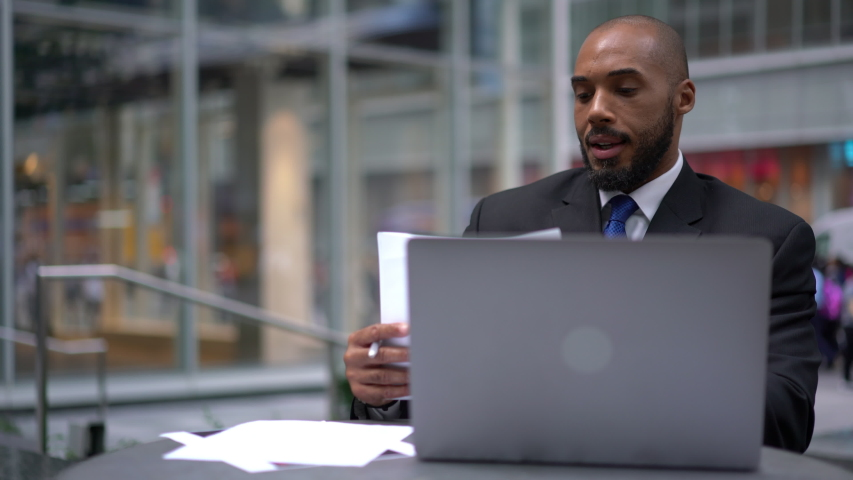Dark skinned man intelligent managing director keyboarding on laptop computer while sitting in cafe terrace, male economist analyzing activities of company via netbook and financial reports | Shutterstock HD Video #1040953838