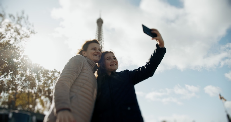 Happy loving mother and daughter taking a selfie photo on a smartphone and cuddling together, on the background of Elfel on a sunny day | Shutterstock HD Video #1040971838