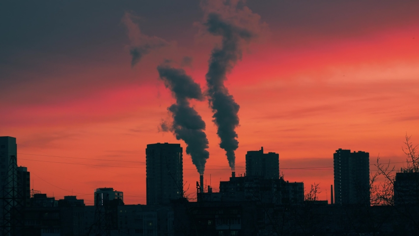 Smokestacks emitting smoke in red sunset sky over dark city skyline silhouette. Timelapse, 4K UHD. | Shutterstock HD Video #1040993138