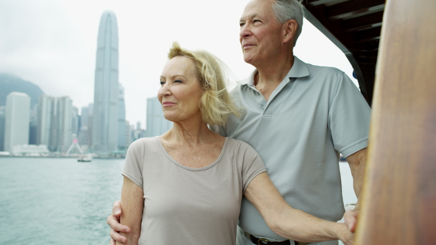 Senior Caucasian retirement couple enjoying their anniversary cruise on board a junk in Victoria harbor Hong Kong RED MONSTRO | Shutterstock HD Video #1040997098